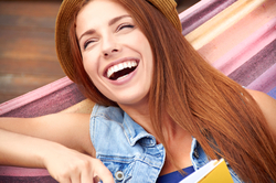 A young woman smiling broadly, her teeth straight and uniform after Invisalign® treatment